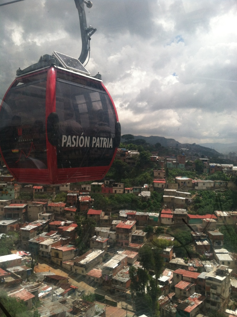 "One of the MetroCable Cars. This one says Pasión Patria, or Passion for the Fatherland. Others say ""Love,"" ""Freedom,"" etc."