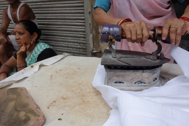 Woman ironing clothes in Chandni Chowk, Delhi, India